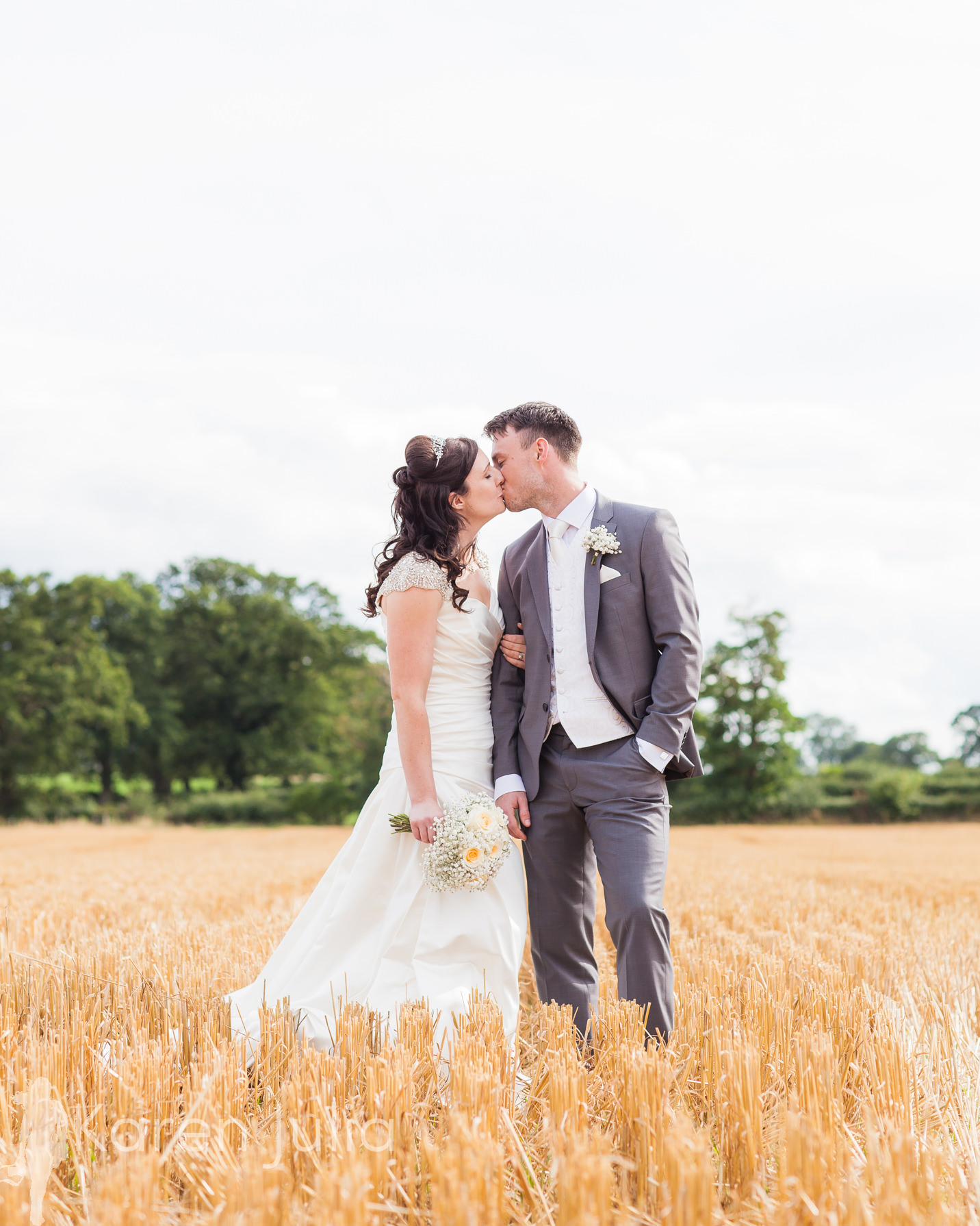 bride and groom in freshly cut cornfield , Cheshire