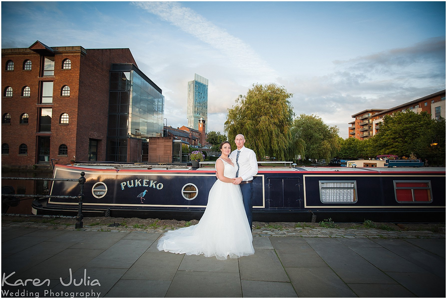 bride and groom pose for a wedding day portrait in Castlefield with canal in background