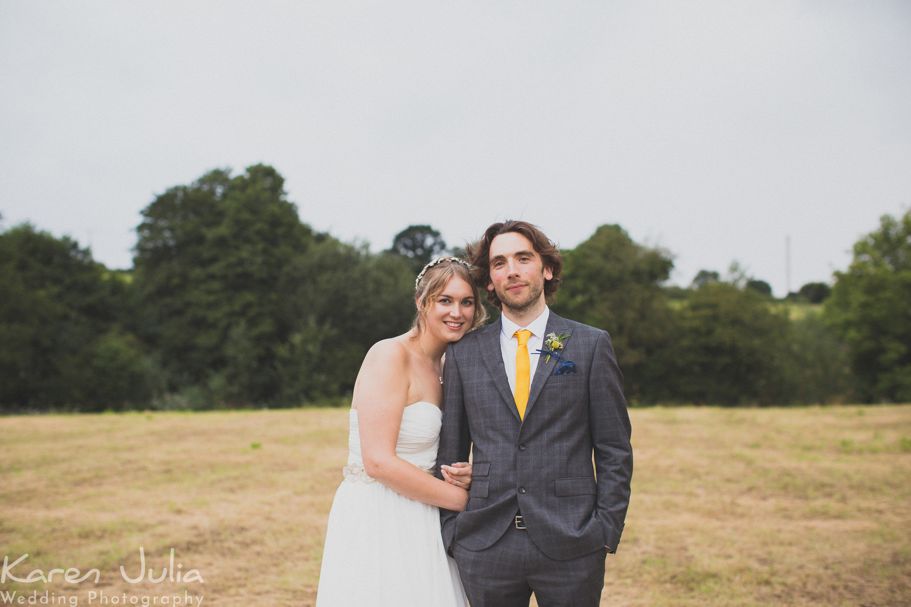 Rustic Village Hall Wedding Photography featuring bride and groom in field