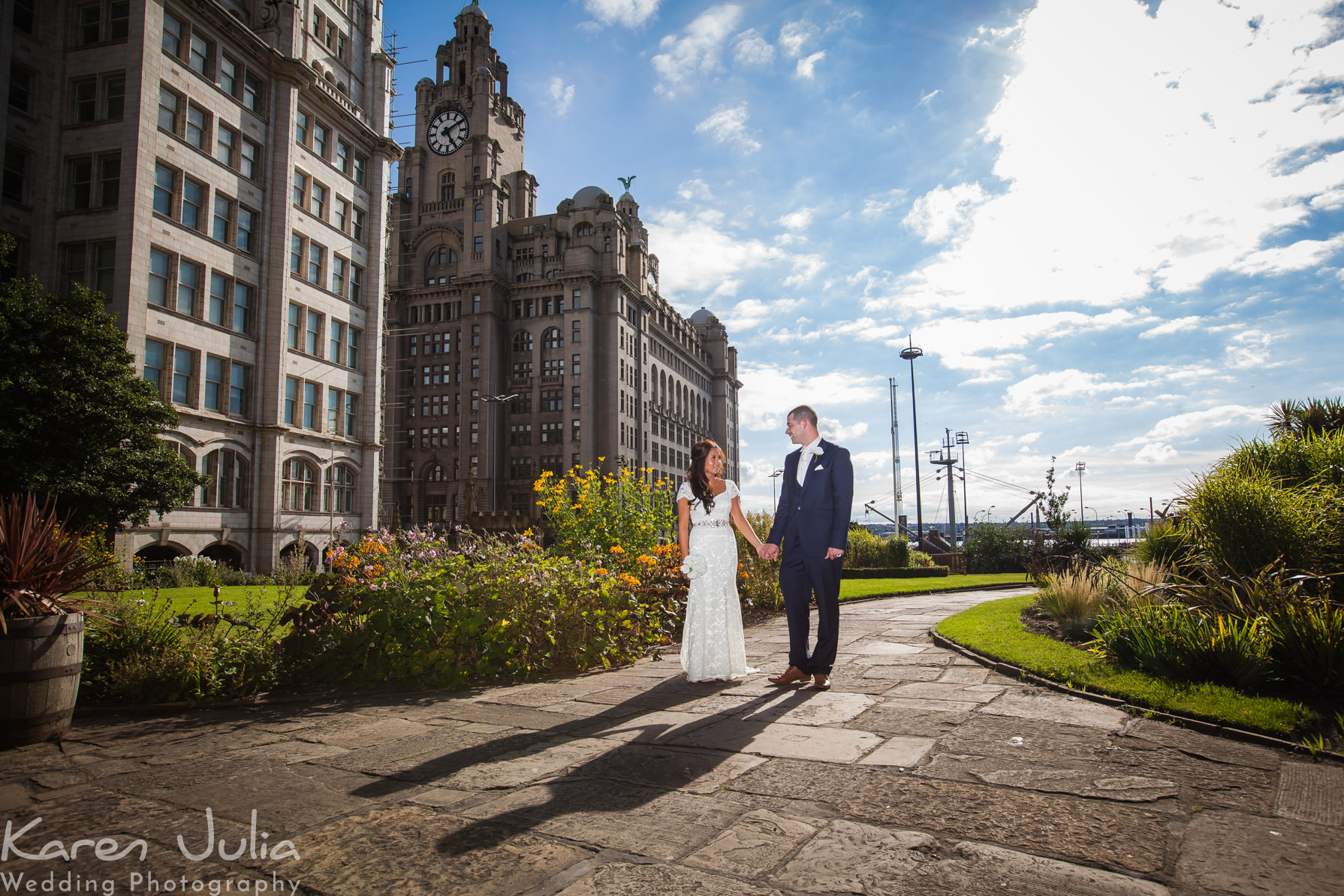 bride and groom walk through church gardens with Liver building in background