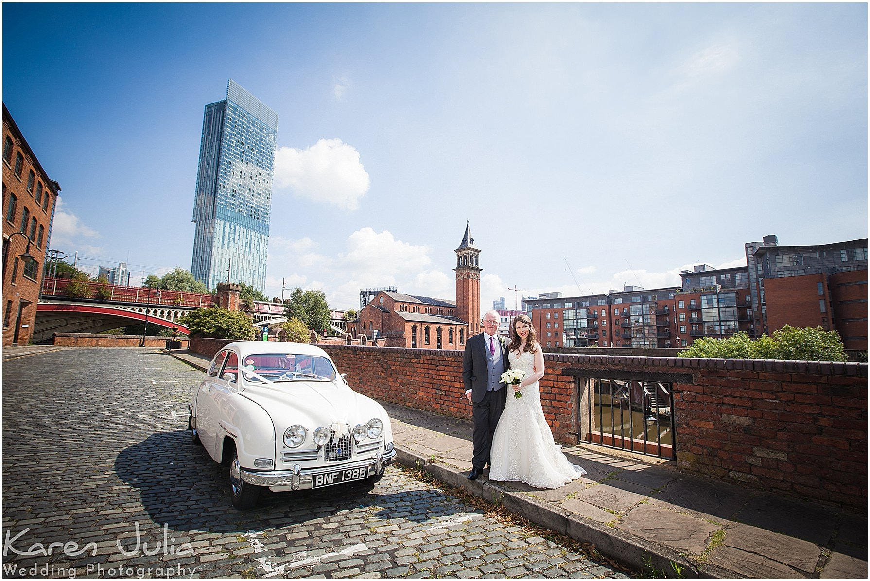 bride and dad pose with vintage SAAB wedding car in Castlefield Manchester