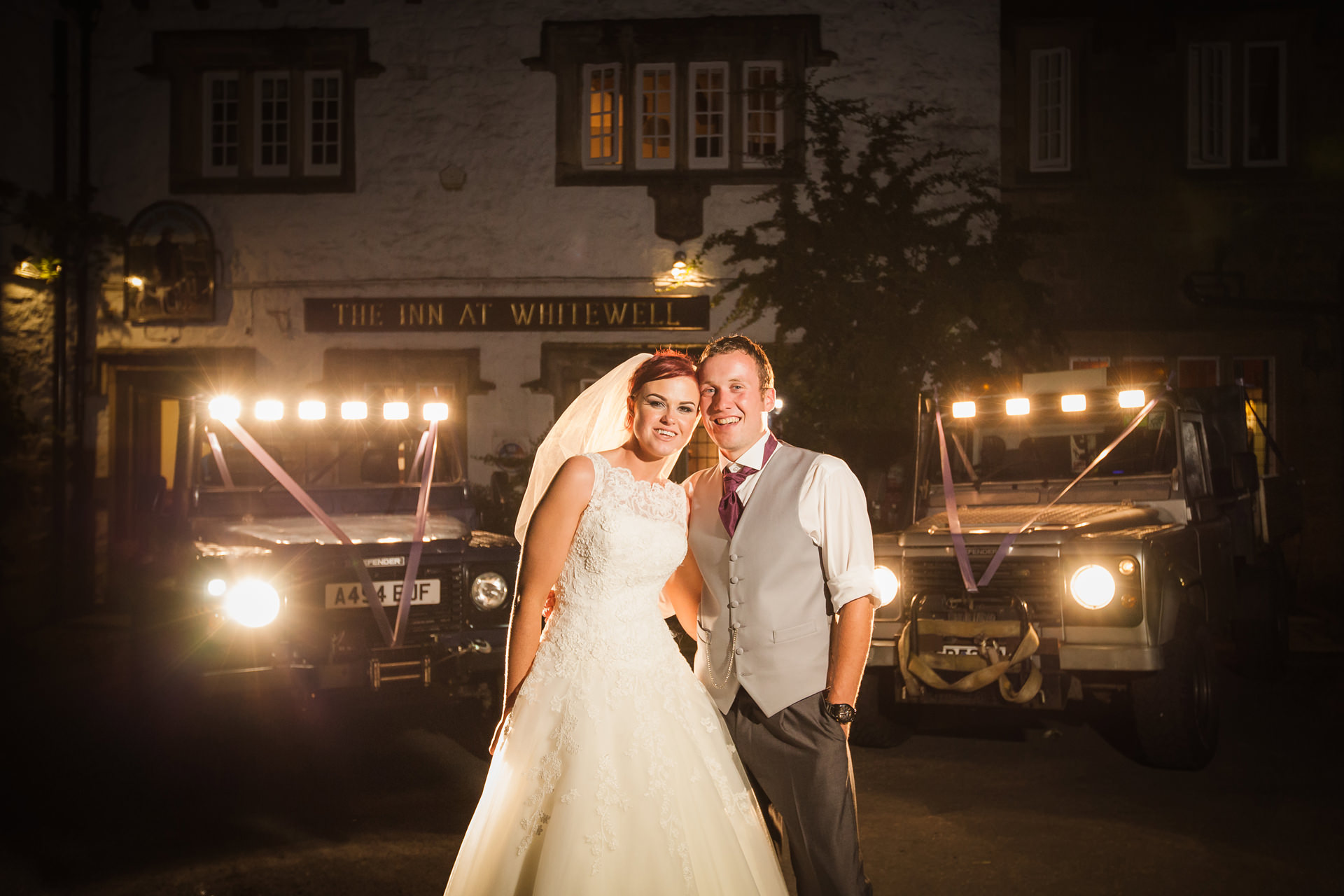 Inn at Whitewell wedding photography; bride and groom night portrait in front of land rovers on their wedding day