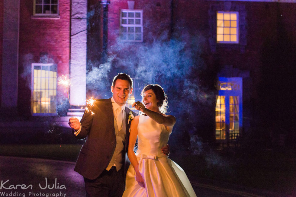 bride and groom holding sparklers for a photo at their autumn wedding