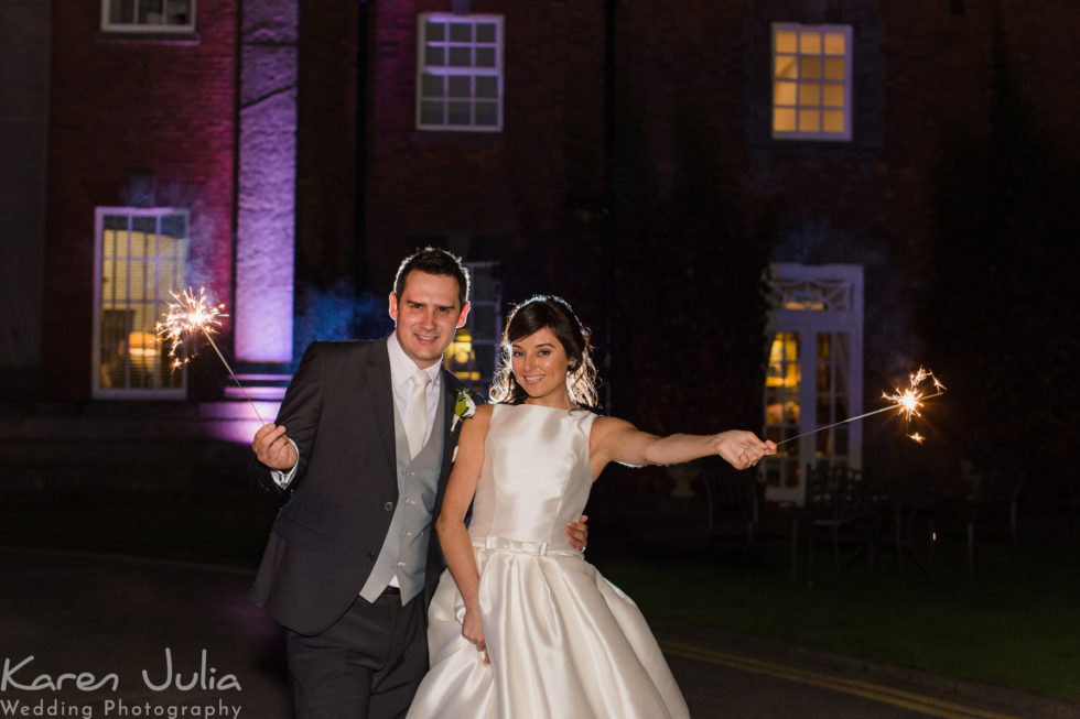 bride and groom pose for a portrait with sparklers outside Mottram Hall