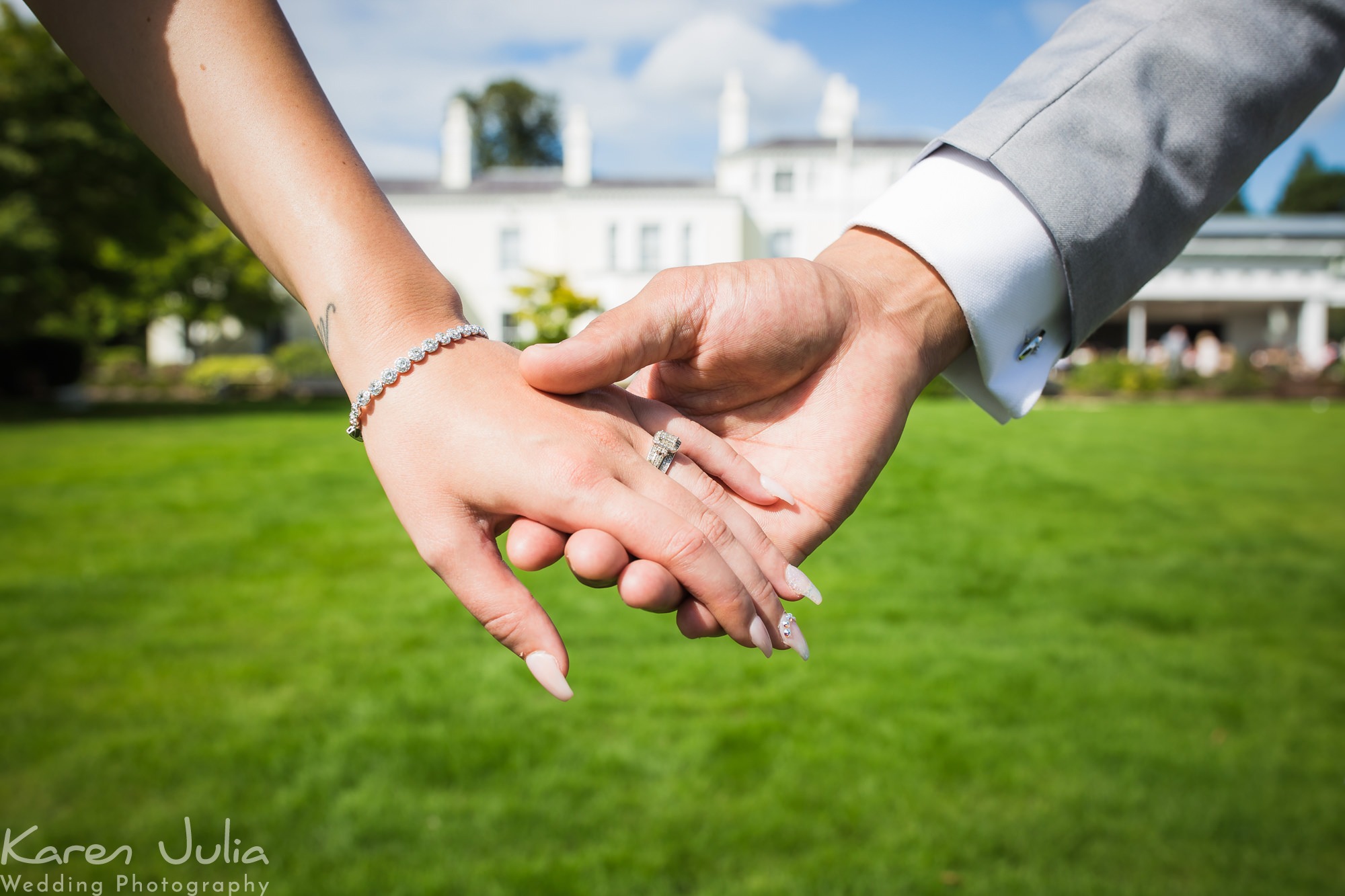 bride and groom detail shot of hands with the wedding venue Chancellors Hotel in the background