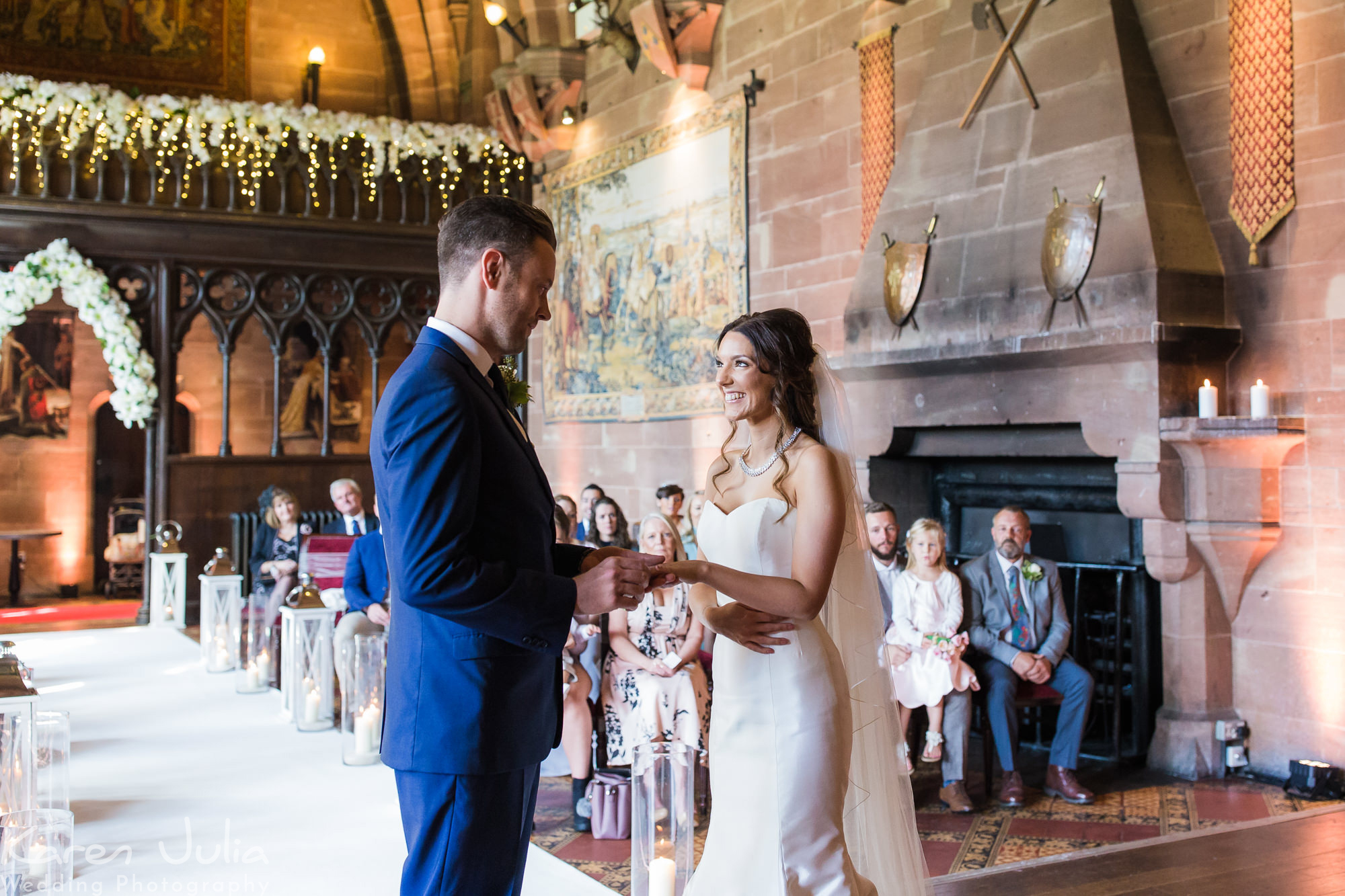 bride and groom exchange rings during wedding ceremony at Peckforton Castle